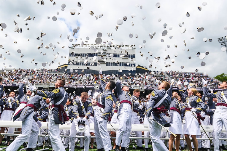 Graduates at a stadium toss their hats into the air after a ceremony.
