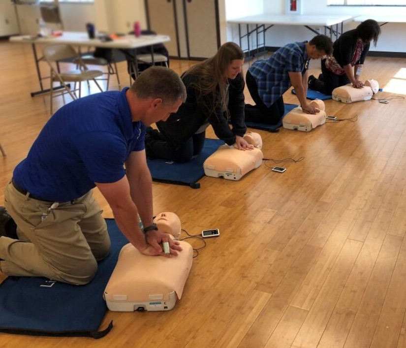 Four class members practice CPR compressions on training body.