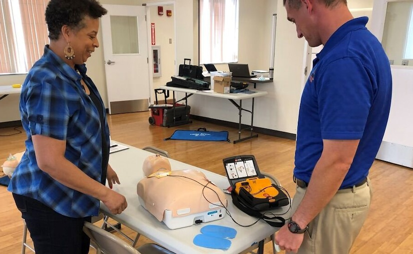 Woman and man stand at a table with a CPR training body and AED.