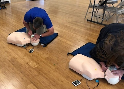 Man and woman practice CPR on training body.