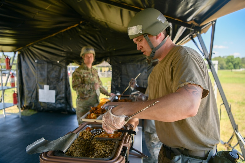 Tech. Sgt. Jonathan Ardis, 628th Force Support Squadron readiness NCOIC, prepares a plate for Col. Bobby Degregorio, 315th Mission Support Group commander within the Single Pallet Expeditionary Kitchen, during exercise Palmetto Challenge, May 21, 2019, at Joint National Guard Base McEntire, S.C.