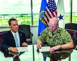 A civilian and military man sit at a table with papers in front of them.