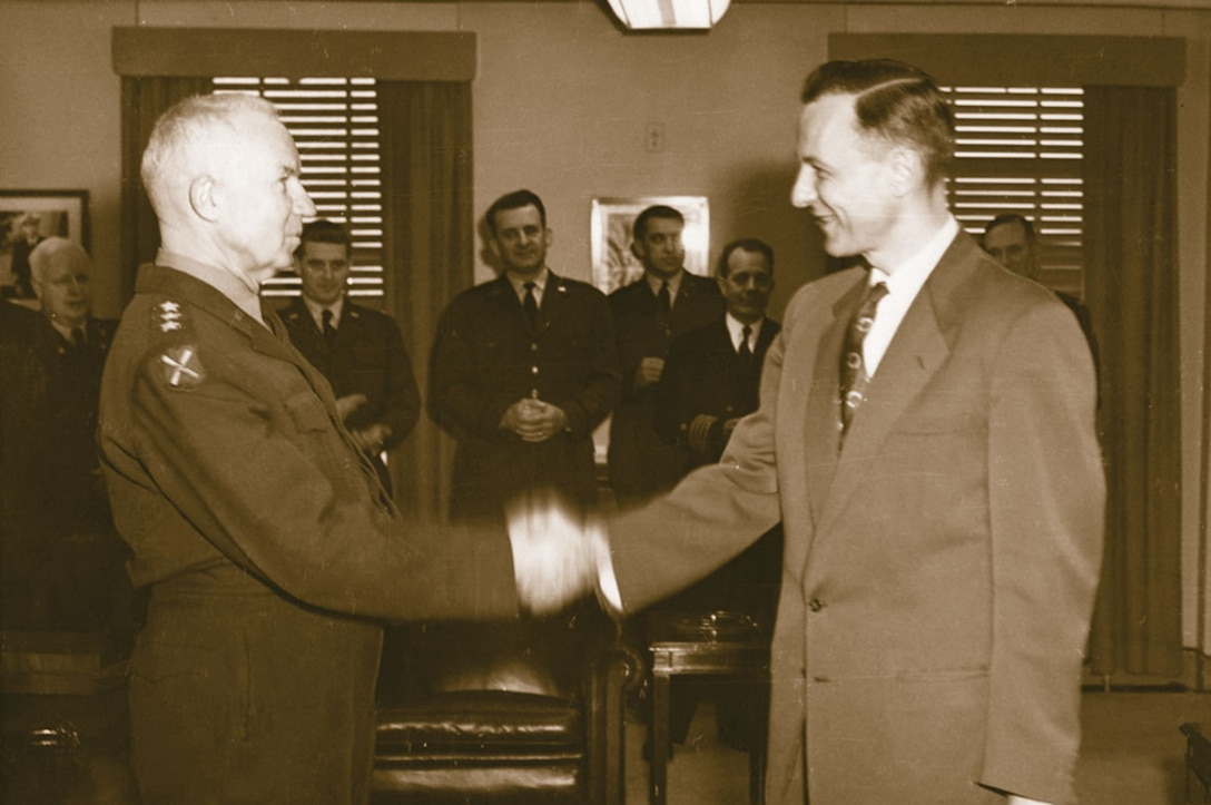 NSA Director Lieutenant General Ralph J. Canine, USA, shakes hands with Louis W. Tordella