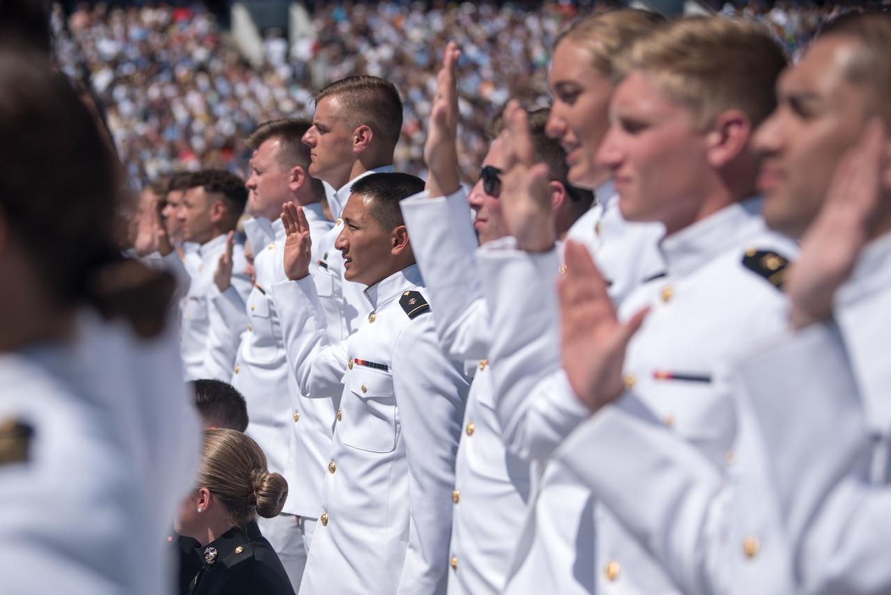 Uniformed men and women raise their right hands.