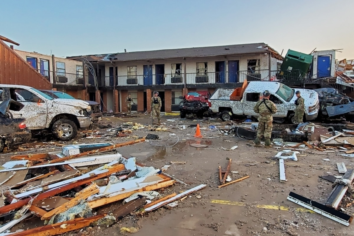 Service members walk among tornado debris in front of a motel.