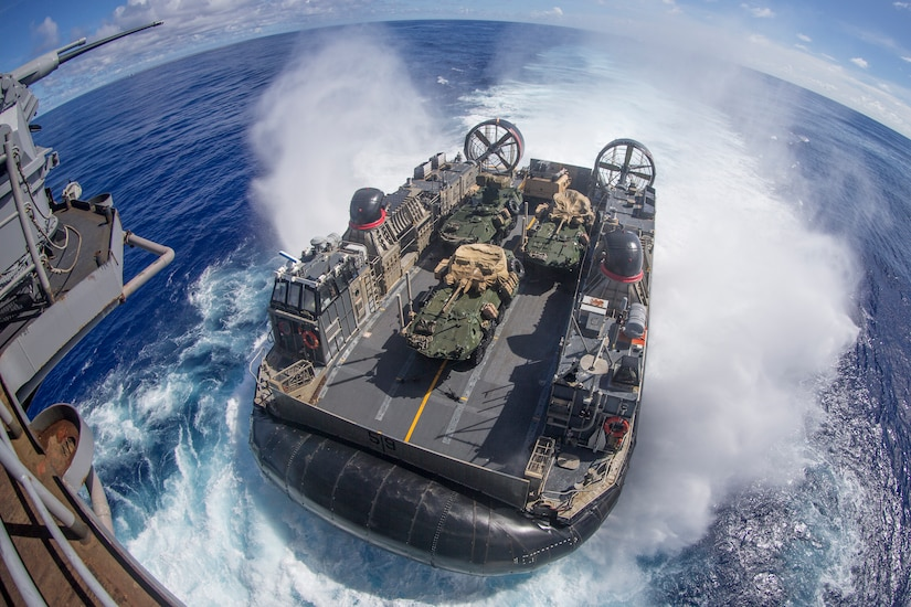 A boat carrying military vehicles splashes into the water.