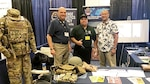 DLA Acquisition Director Matthew Beebe (left) poses for a photo at the 2019 AUSA LANPAC Symposium and Exposition in Honolulu May 21-23 with Steve Dirico and Geoff Ellazar