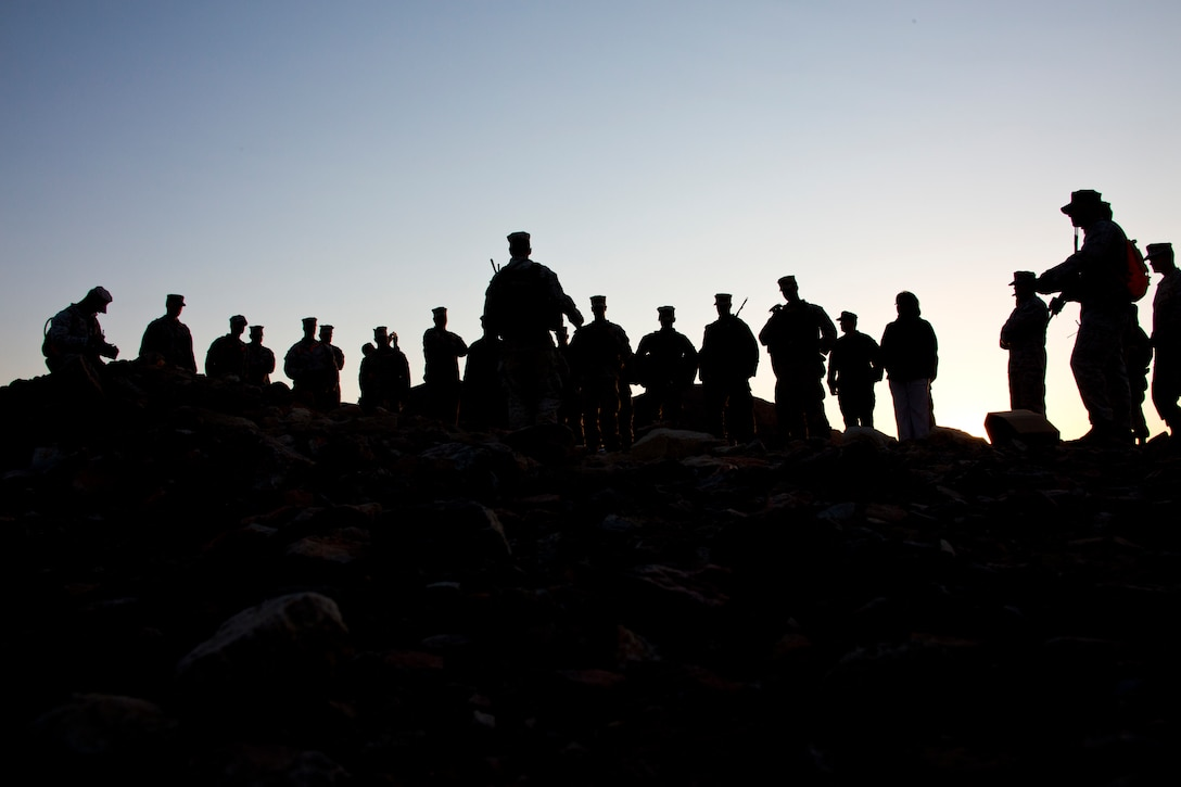 More than a dozen Marines in silhouette gather for a briefing.