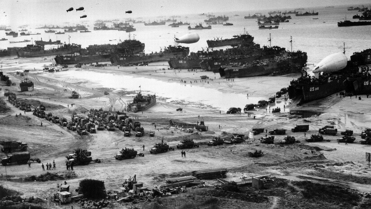 Ships, U.S. and Allied service members, and military trucks arrive on the beaches of Normandy.