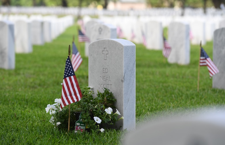 American flags are displayed in front of tomb stones at the Biloxi National Cemetery Memorial Day Ceremony in Biloxi, Mississippi, May 27, 2019. The ceremony honored those who have made the ultimate sacrifice while serving in the armed forces. Biloxi National Cemetery is the final resting place of more than 23,000 veterans and their family members. Eight hundred burials take place there every year for men and women who served in wars years ago and for those defending America today. (U.S. Air Force photo by Kemberly Groue)