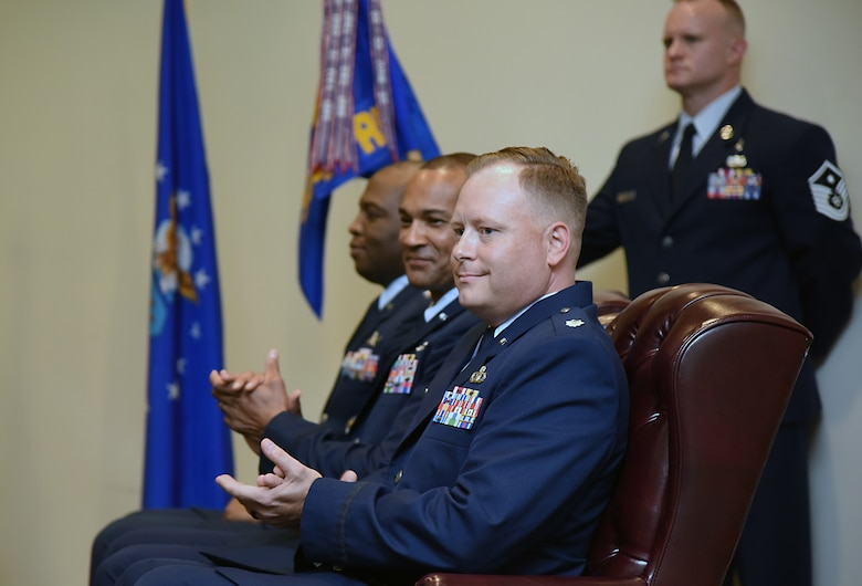 U.S. Air Force Col. Leo Lawson, Jr., 81st Training Group commander, Lt. Col. Billy Wilson, Jr., outgoing 334th Training Squadron commander, and Lt. Col. Harry James, incoming 334th TRS commander, sit on stage during the 334th TRS change of command ceremony in the Roberts Consolidated Aircraft Maintenance Facility at Keesler Air Force Base, Mississippi, May 23, 2019. James assumed command from Wilson with the passing of the guidon. The passing of the guidon is a ceremonial symbol of exchanging command from one commander to another.. (U.S. Air Force photo by Kemberly Groue)