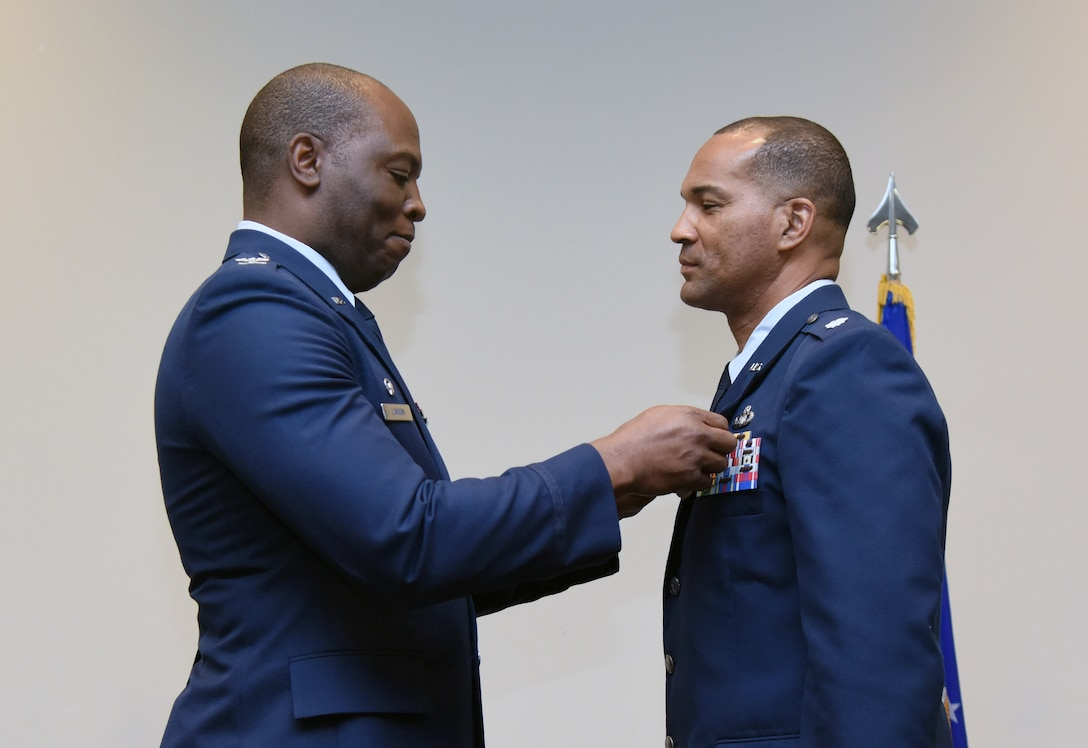 U.S. Air Force Col. Leo Lawson, Jr., 81st Training Group commander, presents the Meritorious Service medal to Lt. Col. Billy Wilson, Jr., outgoing 334th Training Squadron commander, during the 334th TRS change of command ceremony in the Roberts Consolidated Aircraft Maintenance Facility at Keesler Air Force Base, Mississippi, May 23, 2019. Wilson passed on command to Lt. Col. Harry James during the ceremony. (U.S. Air Force photo by Kemberly Groue)
