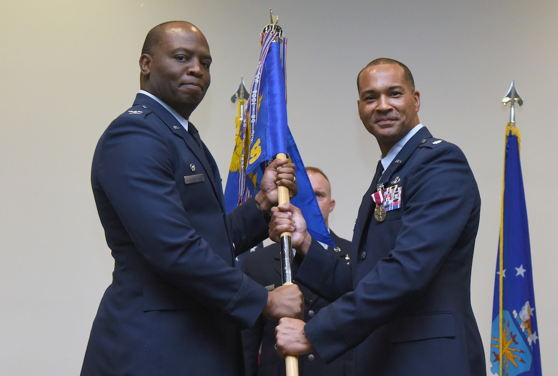 U.S. Air Force Col. Leo Lawson Jr., 81st Training Group commander, takes the 334th Training Squadron guidon from Lt. Col. Billy Wilson, Jr., outgoing 334th TRS commander, during the 334th TRS change of command ceremony in the Roberts Consolidated Aircraft Maintenance Facility at Keesler Air Force Base, Mississippi, May 23, 2019. The passing of the guidon is a ceremonial symbol of exchanging command from one commander to another. (U.S. Air Force photo by Kemberly Groue)