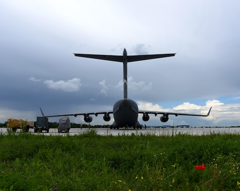 A C-17 Globemaster III from the 60th Air Mobility Wing is parked near the flightline at the Henri Coanda International Airport May 25, 2019, in Bucharest, Romania. U.S. Air Force personnel worked with members of the Romanian armed forces to load the C-17 with cargo and equipment that would then be delivered to Afghanistan in support of NATO's Resolute Support mission. Romania is the sixth largest contributor of troops to RS with more than 730 personnel deployed. (U.S. Air Force photo by 2nd Lt. R. Michael Longoria)