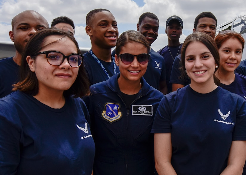 Nine Air Force recruits in blue Air Force T-shirts stand with an Air Force officer in a flight suit for a photo.
