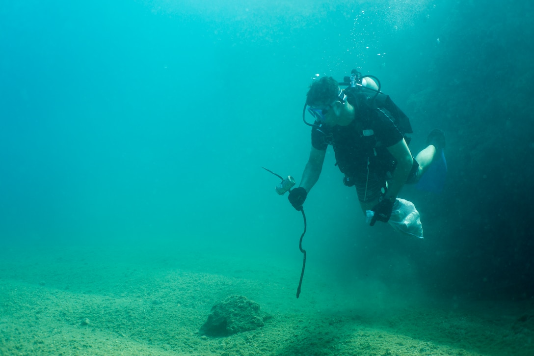 Petty Officer 1st Class Dustin Cormier, a hospital corpsman with 3rd Medical Battalion, 3rd Marine Logistics Group, looks for trash during a scuba beach cleanup May 26, 2019 at Sunabe North Steps, Okinawa, Japan.