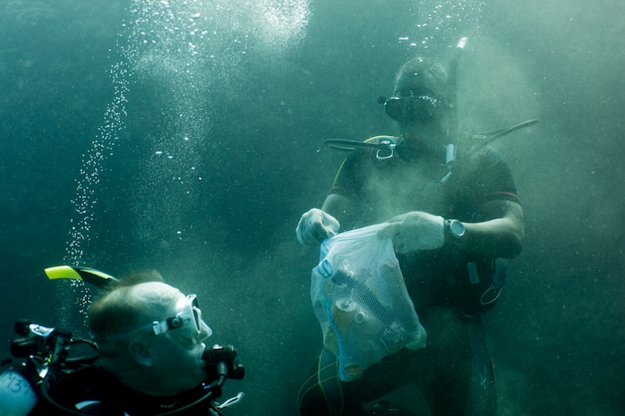 Petty Officer 2nd Class Alan Gooden, a hospital corpsman with 3rd Medical Battalion, 3rd Marine Logistics Group, stuffs a can in a mesh bag during a scuba beach cleanup May 26, 2019 at Sunabe North Steps, Okinawa, Japan.