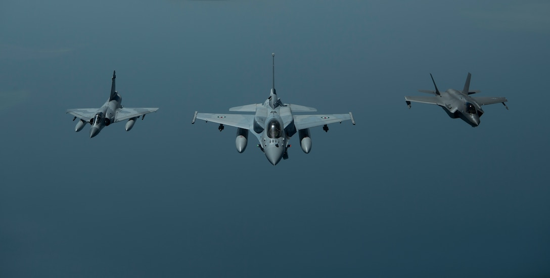 A photo of two UAE aircraft and a US aircraft flying in formation.