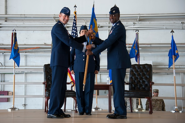 U.S. Air Force Col. Stephen Snelson, the 6th Air Mobility Wing commander, passes the 6th Operations Group guidon to incoming commander Col. Travis Edwards, during an assumption of command ceremony at MacDill Air Force Base, Fla., May 23, 2019. During Edwards's previous assignment, he served as the U.S. Transportation Command's Senior Liaison Officer to European Command and the North Atlantic Treaty Organization in U.S. Army Garrison Stuttgart, Germany.