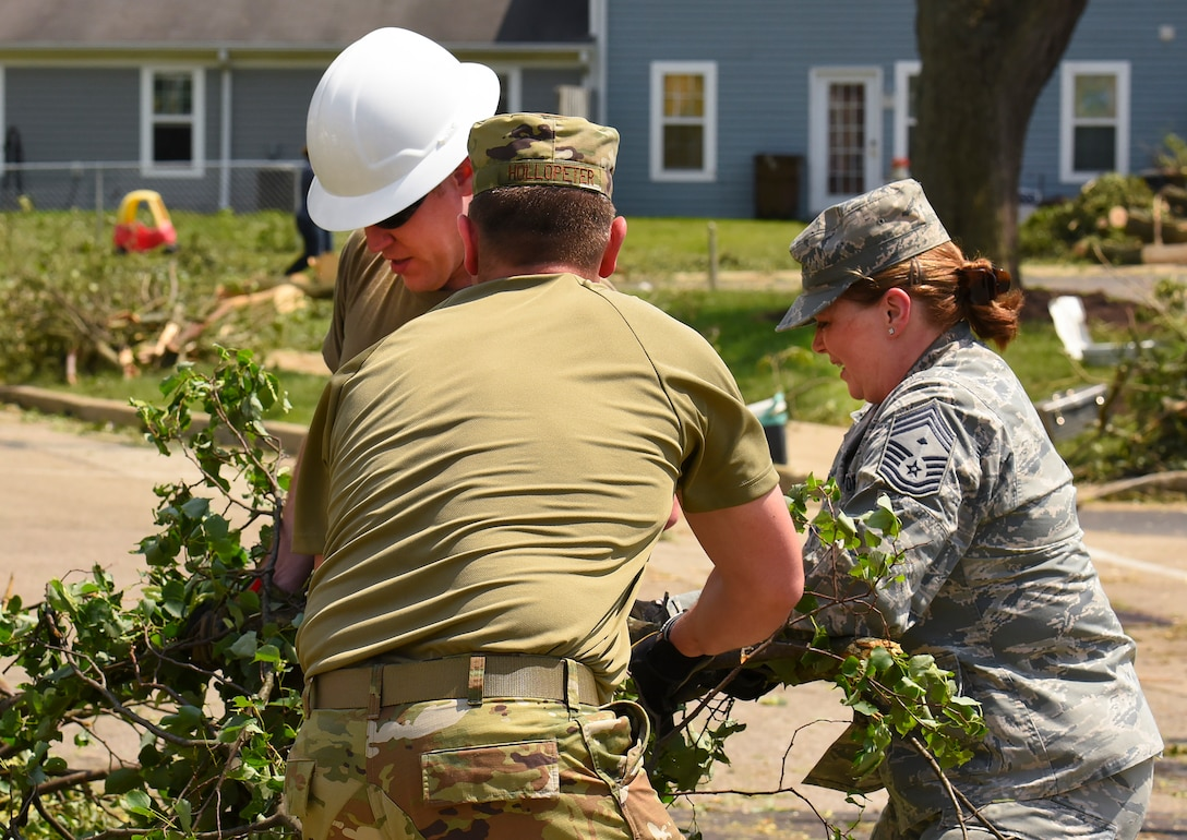 Chief Master Sgt. Jennifer Hellwig, Air Force Materiel Command first sergeant work to clear tree branches during recovery operations.  Residents worked alongside other volunteers from around Wright-Patterson AFB and base emergency responders to ensure everyone's safety and begin the cleanup process. (U.S. Air Force photo by R.J. Oriez)