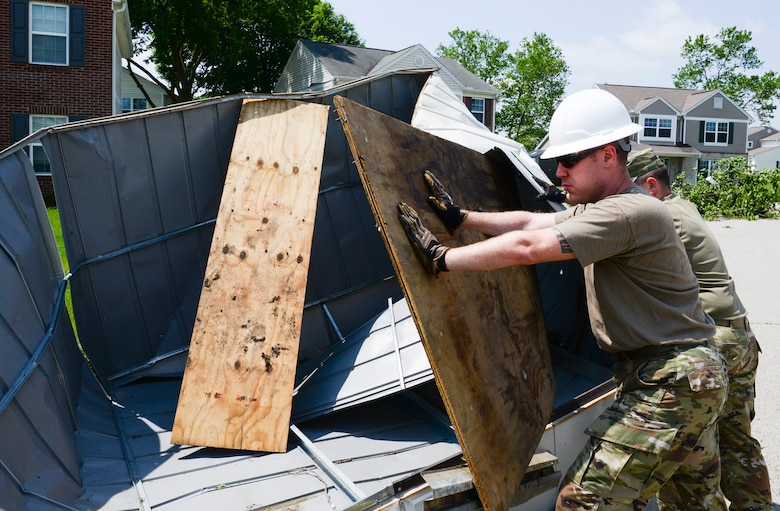 Staff Sgt. Michael Olson, National Air and Space Intelligence Center, helps to remove a shed from the front yard of someone's home during recovery operations. Residents worked alongside other volunteers from around Wright-Patterson AFB and base emergency responders to ensure everyone's safety and begin the cleanup process. (U.S. Air Force photo by R.J. Oriez)