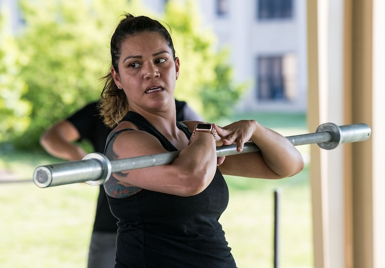 Master Sgt. Betsy Bonilla, 436th Airlift Wing 3F5 base functional manager, looks to see if she has proper form during one of the Warrior Fitness exercises May 16, 2019, at the Fitness Center on Dover Air Force Base, Del. Bonilla has participated in Warrior Fitness programs offered at numerous duty assignments since 2010. (U.S. Air Force photo by Roland Balik)