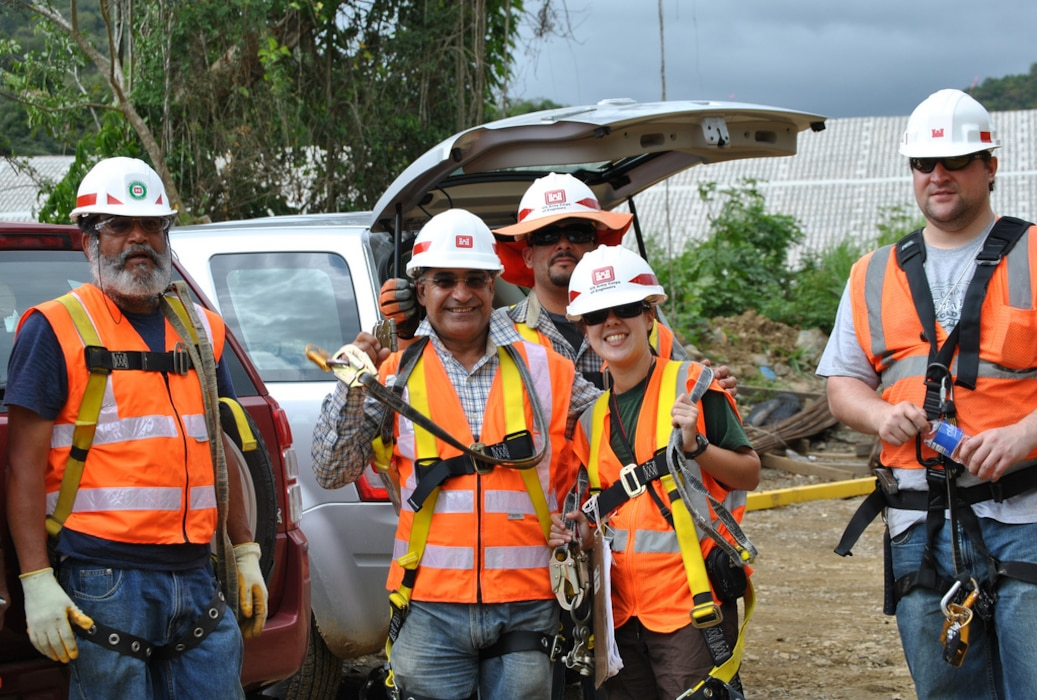 five individuals standing wearing Personal protective equipment