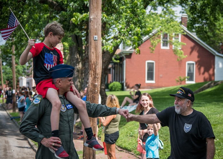 "Col. Glenn Collins, commander, 932nd Airlift Wing, with his son perched on his shoulders, gives a fist bump of appreciation to an Air Force veteran during the Belleville Memorial Day Parade, May 27, 2019, Belleville, Illinois. ""What an absolute privilege to be able to participate in the Belleville Community Parade where we honor those who sacrificed so much for each of us, while connecting with our community and reaffirming bonds with former service members,"" said Collins. (U.S. Air Force photo by Christopher Parr)"