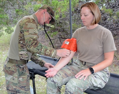 Staff Sgt. Alexander Bach, 232nd Medical Battalion, checks 1st Lt. Elena Haymond's blood pressure during the Subjective Objective Assessment Plan, or SOAP, notes lane. Incorporating SOAP notes was a new lane in this year's Trinity competition. This provided the competitors an opportunity to test their medical knowledge and patient observations in a more rigorous simulated field environment.
