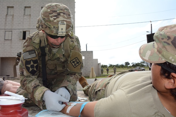 Competing in the Tactical Combat Casualty Care lane, Staff Sgt. Eric Bradley, 232nd Medical Battalion, prepares to start administering a whole blood simulation to an AIT Soldier.