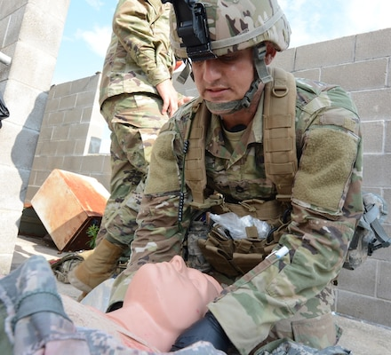 Sgt. 1st Class David Nagle, Medical Professional Training Brigade, checks a simulated patient for injuries while competing in the Tactical Combat Casualty Care lane. The annual Trinity Competition is a grueling, four day event to determine the division level Best Warrior, Drill Sergeant of the Year and Best Medic.