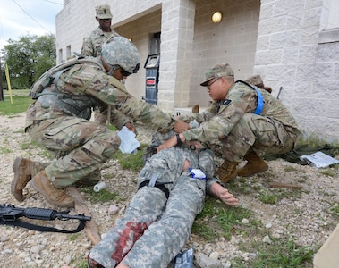 Drill Sergeant Jeffrey Lullen (left), 264th Medical Battalion, asseses a simulated patient during the Tactical Causality Combat Care lane.