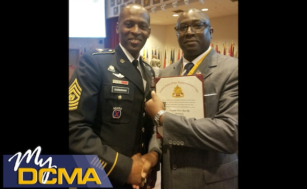 Man in Army uniform shakes the hand of another man wearing a business suit