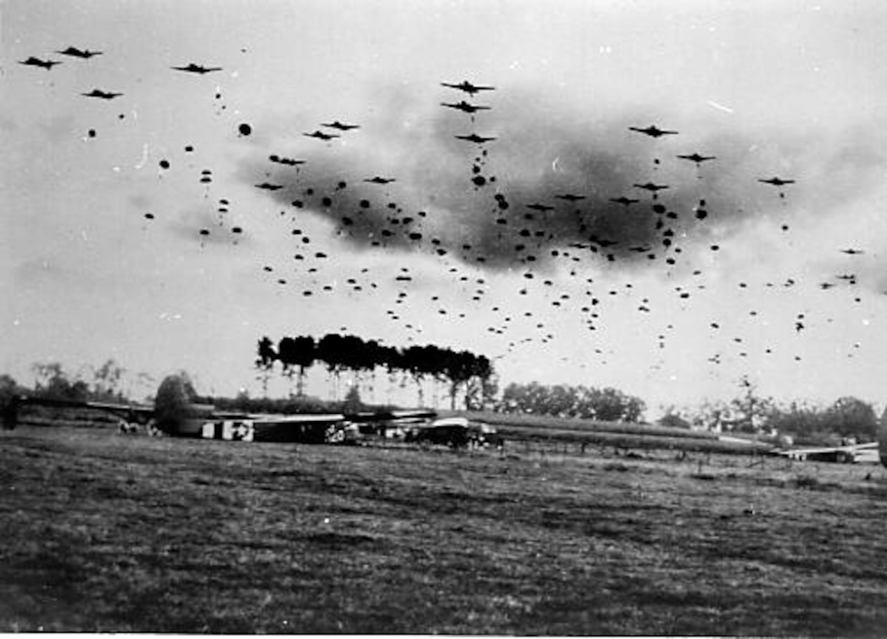 Multiple aircraft fly over a landing zone.