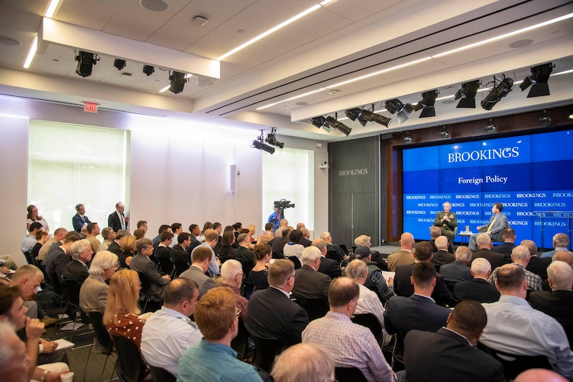 Audience in foreground as Joint Chiefs chairman participates in moderated discussion.