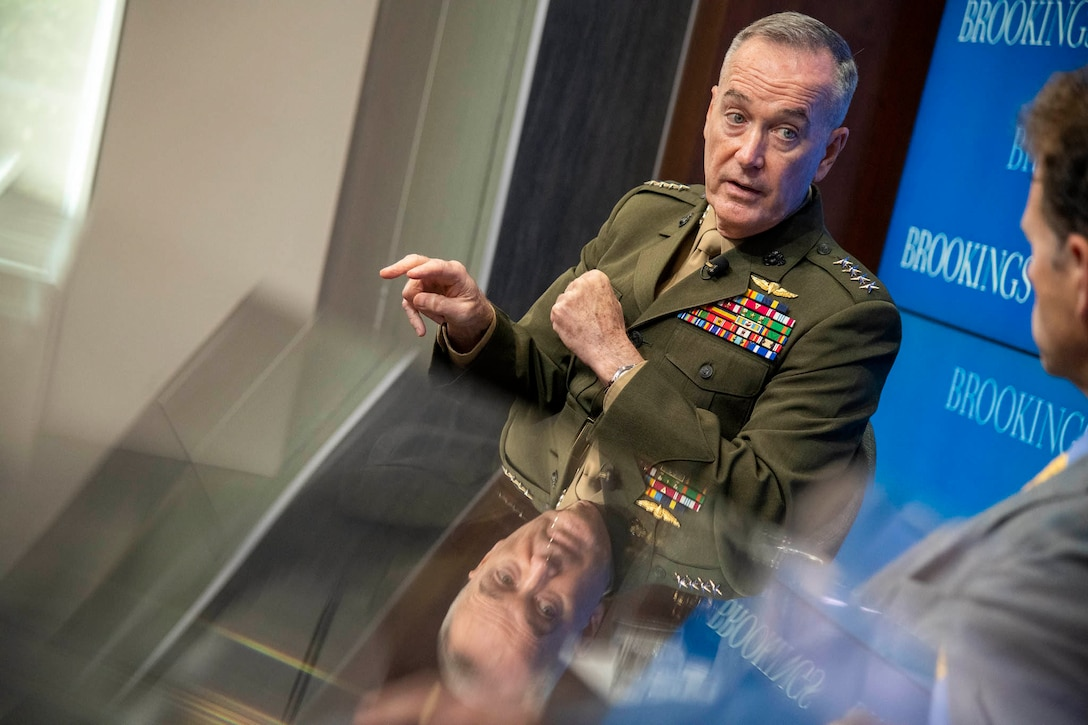 Marine general gestures while talking with civilian.