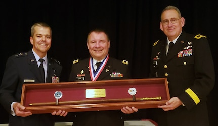 Air Force Maj. Gen. John DeGoes (left), 59th Medical Wing commander, and Army Brig. Gen. George Appenzeller (right), Brooke Army Medical Center commanding general, present the 2019 Gold Headed Cane Award to Army Col. (Dr.) Andrew Cap, chief of coagulation and blood research at the U.S. Army Institute of Surgical Research, during the San Antonio Uniformed Services Health Education Consortium awards dinner May 18 at the Parr Club at Joint Base San Antonio-Randolph. The Gold Headed Cane Award focuses on four areas: patient care, resident teaching, clinical research and operational medicine.