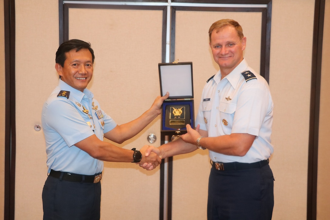 U.S. Air Force Maj. Gen. Russell Mack, Pacific Air Forces (PACAF) deputy commander, receives a gift from Air Vice Marshal Johanes Berchmans, Assistant to the Chief of Staff for Operations, Tentara Nasional Indonesia Angkatan Udara, or TNI AU (Indonesian Air Force), during the 11th annual Indonesian Air Force-PACAF Airman-to-Airman talks in Denpasar, Indonesia, May 16, 2019.