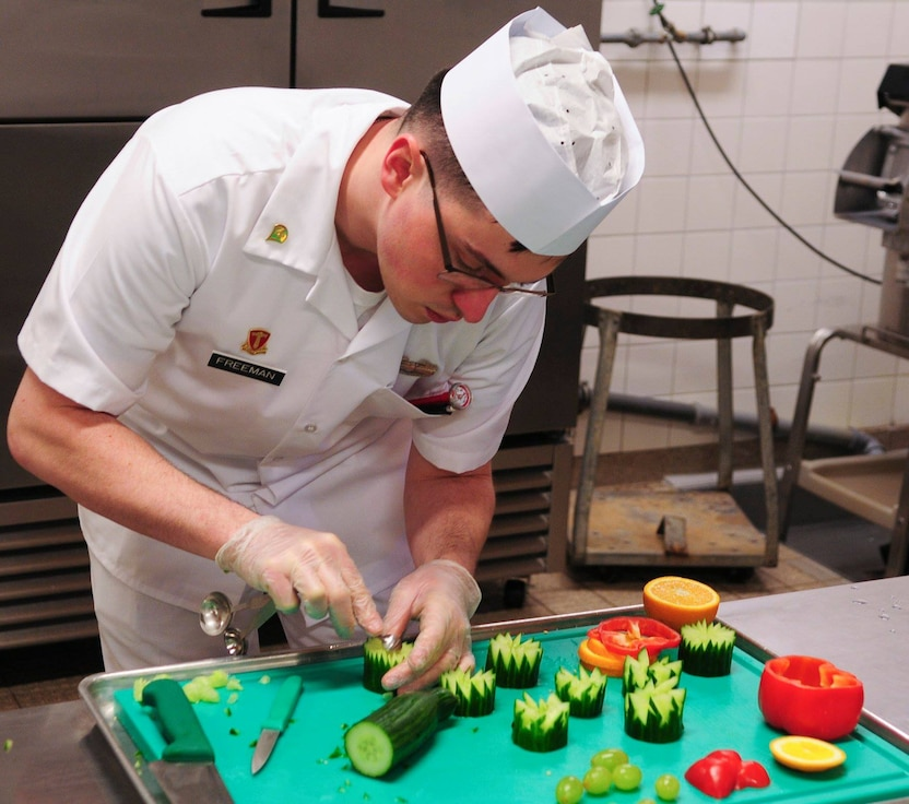 Spc. Dustin Freeman a cook with the 66th Transportation Company prepares garnishing for the lunch menu during the final evaluation of the Philip A. Connelly Award competition at the Clock Tower Cafe, Kleber-Kaserne.
