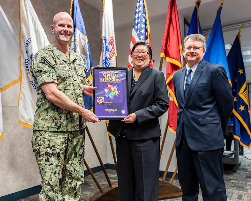 Event guest speaker being presented a memento of appreciation by two members of DLA Land and Maritime command staff.