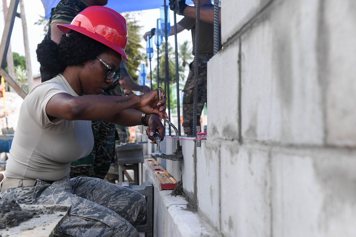 A U.S. Air Force engineer lays bricks.