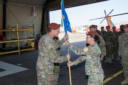 Maj. Amoreena York, Aviation Company (AVCO) commander, Task Force Sinai, passes the AVCO guidon to Col. Mark Ott, Task Force Sinai commander, symbolizing the relinquishment of command at South Camp, Egypt, May 23, 2019. AVCO supports rotary-wing aviation mission requirements for the Multinational Force & Observers (MFO). The MFO is headquartered in Rome, is an independent international organization, created by agreement between the Arab Republic of Egypt and the State of Israel, with peacekeeping responsibilities in the Sinai.