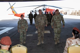 Maj. Amoreena York, Col. Mark Ott, and Maj. Mark Axtell walk to their seats after passing the guidon signaling the transfer of leadership of Aviation Company (AVCO), Task Force Sinai,  South Camp, Egypt, May 23, 2019. AVCO is a self-sustaining aviation company, enhanced with all the support elements of a traditional aviation battalion.