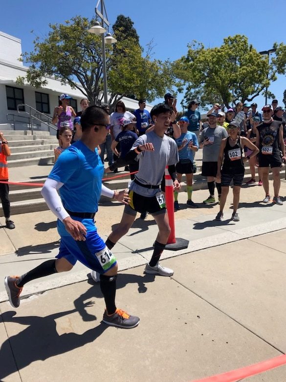 Master Sgt. Anthony Chua, 614th Air Operation Center operations division flight chief, tags in his son as he finishes a leg of the So Cal Ragnar Relay Ultramarathon, April 12 through 13, 2019, in Huntington Beach, Calif. The team completed the race in 29 hours, 6 minutes and 33 seconds, finishing in first place for the Military Men's Ultra category. (Courtesy photo)