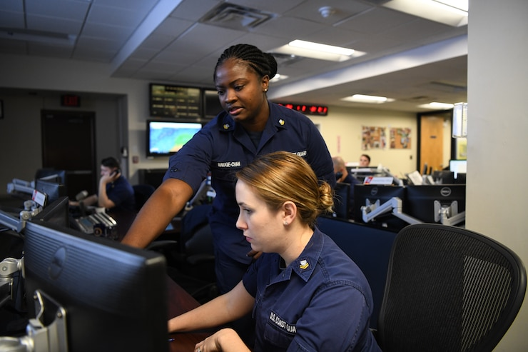 Petty Officer 1st Class Lecia Mauge-Chan (standing) and Petty Officer 2nd Class Amanda Lewis (seated) stand the watch as operations specialists in the command center of Coast Guard Sector Hampton Roads in Portsmouth, Virginia, March 20, 2019.