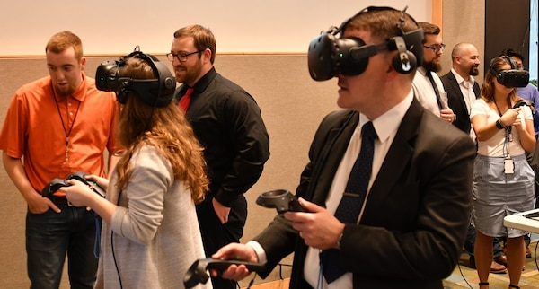 IMAGE: KING GEORGE, Va. (May 22, 2019) – Three attendees engage in a virtual reality visualization of Navy ships – inside and out – at the first annual Modeling and Simulation Summit sponsored by the Naval Surface Warfare Center Dahlgren Division. Two engineers fly around the topside of Navy ships via virtual reality while a third explores the interior of an amphibious transport dock ship's pilot house. 
