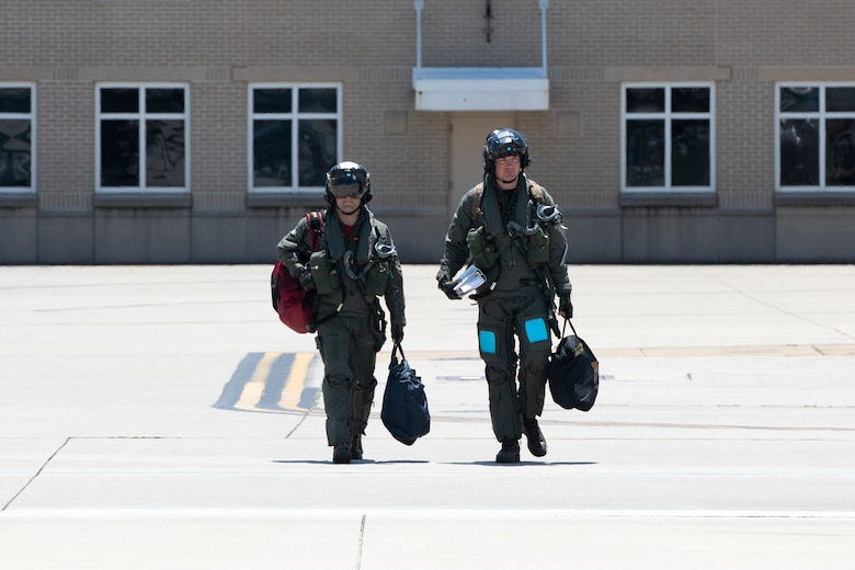 Two U.S. Navy pilots walk to the fly out VFA-101's last F-35C Lightning II to depart Eglin Air Force Base, Florida, May 23, 2019.