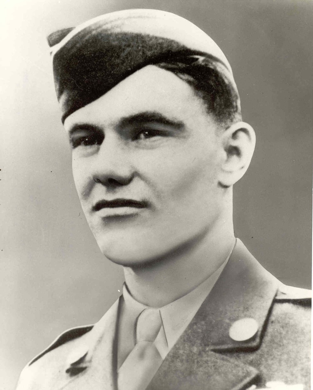 A young man wears an Army uniform and cap.