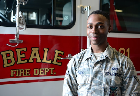 A photo of an Airman posing in front of a firetruck on Beale.
