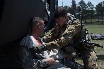 U.S. Army Sgt. Alicia Baum, 1st Battalion 228th Aviation Regiment flight paramedic, assess the injuries of a simulated aircraft casualty during a search and rescue exercise, May 21, 2019, in Comayagua, Honduras. Members from various units on Joint Task Force – Bravo participated in the exercise that simulated a HH-60 Blackhawk crashed during a routine flight carrying personnel. The exercise practiced notification, recall, search and rescue, on-scene medical care, recovery of personnel from low and high angle austere terrain, and medical care once the injured returned to base. (U.S. Air Force photo by Staff Sgt. Eric Summers Jr.)